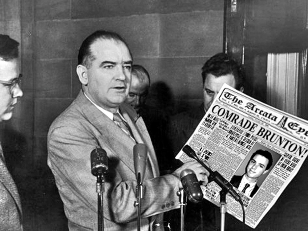 Senator Joseph McCarthy points to newspaper